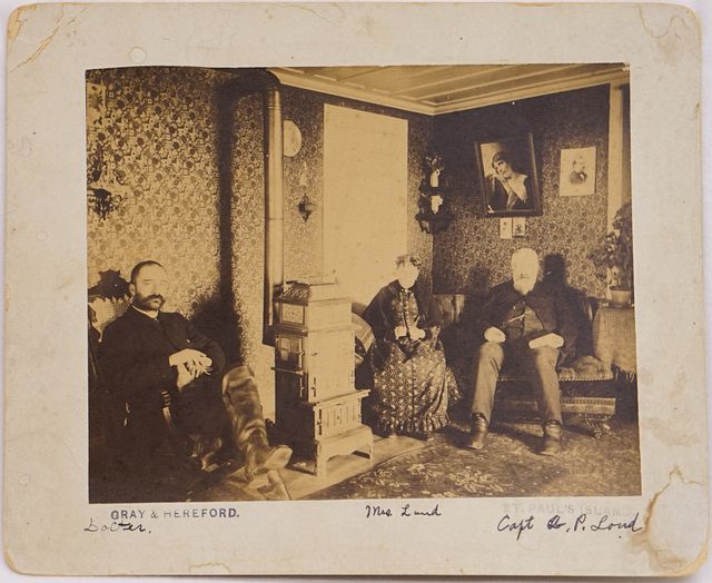 Loud 12, Captain A. P. Loud and Mrs. Loud with doctor, probably Dr. Hareford, inside Government House, St. Paul Island, 1886. Photograph by Gray & Hereford