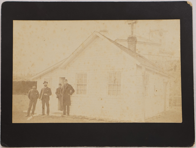 Loud 14, Dr. Hereford (second from left), G. Dallas Hanna (right), and two other men in front of Doctor's house with St. Paul Church of Saints Peter and Paul in background, ca. 1886