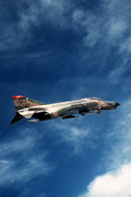 An air-to-air right side view of an F-4E Phantom II aircraft of the 51st Tactical Fighter Wing, Osan Air Base, Republic of Korea. The aircraft is equipped with an ALQ-119 electronic countermeasures pod and an Air Combat Maneuvering Instrumentation (ACMI) pod. (AIRMAN Magazine, Apr 1984)