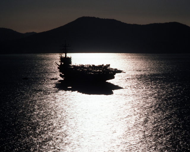 LT. P. J. Azzolina Gulfe du Lion....A silhouetted starboard bow view of the nuclear-powered aircraft carrier USS Dwight D. Eisenhower (CVN-69) anchored off the coast of Toulon, France. OFFICIAL U.S. NAVY PHOTO (RELEASED)