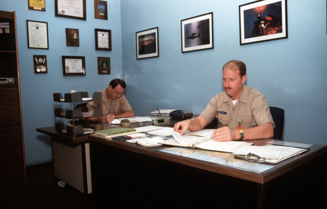 PH2 Landenberger Naval Air Station, Sigonella, Italy....CHIEF Warrant Officer 2 Gilbert C. Neidig, officer-in-charge, Armed Forces Courier Station, and SENIOR CHIEF Cryptologic Technician Gary J. Gentle, foreground, look over the daily paper work. OFFICIAL U.S. NAVY PHOTO (RELEASED)