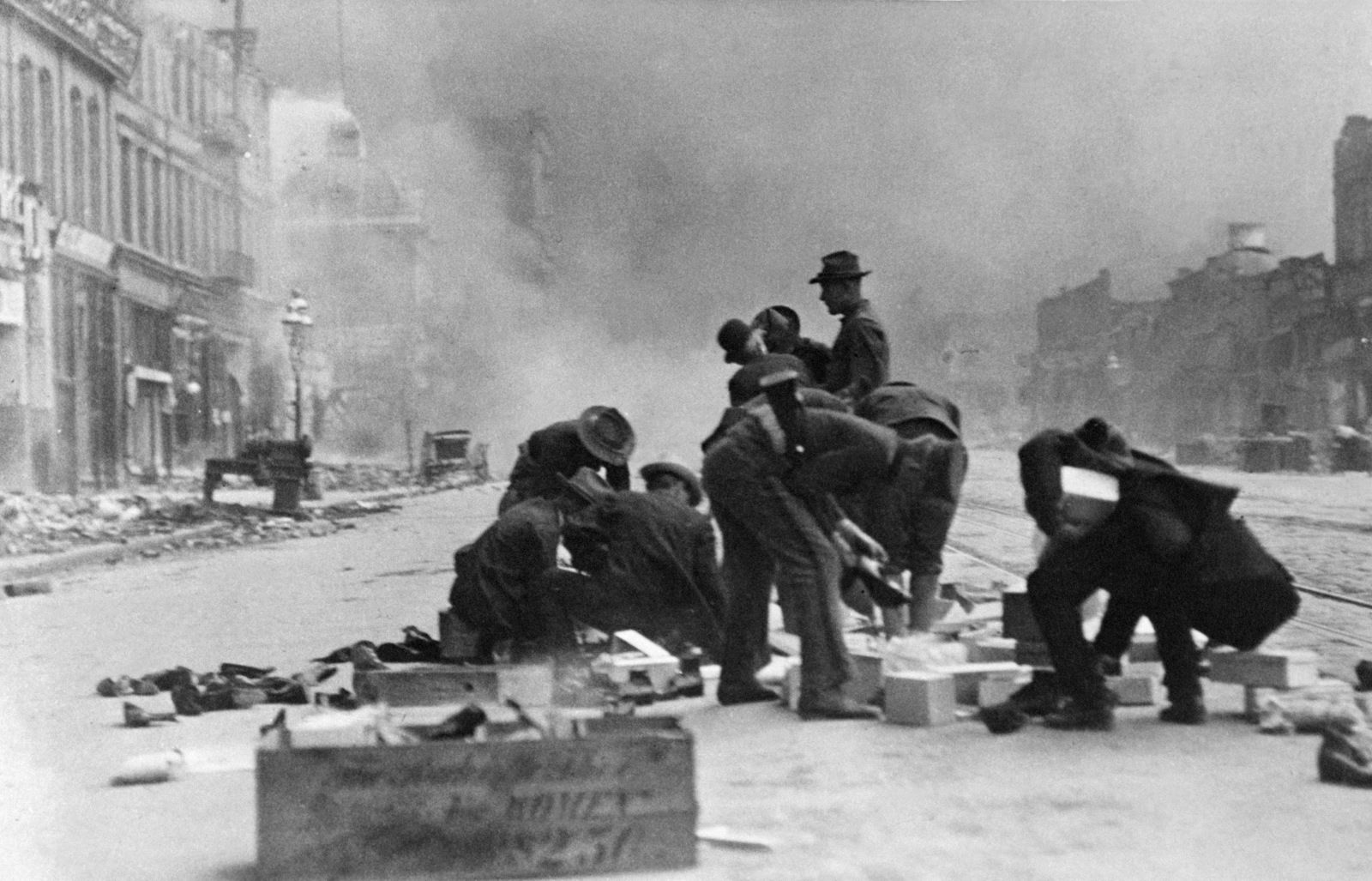 A group of laborers appear to be cleaning building blocks for later use in the rebuilding of San Francisco. A soldier with a Springfield Rifle 03 is picking up something. On April 18, 1906 at 5:15 AM a quake of 8.25 on the Richter scale hit San Francisco. Greater destruction came from the fires afterwards. The city burned for three days. The combination destroyed 490 city blocks and 25,000 buildings, leaving 250,000 homeless and killing between 450 and 700. Estimated damages, over $350 million