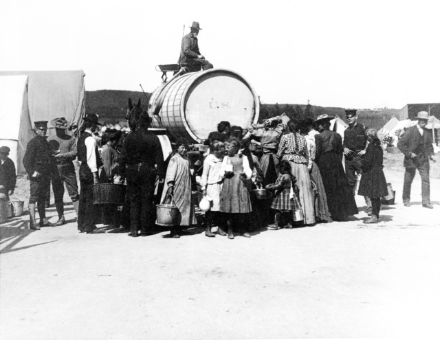 Fresh water is delivered via mule drawn barrel wagon to the refugees at a camp in the Presidio. Military personnel stand by as women and children bring buckets to fill. On April 18, 1906 at 5:15 AM a quake of 8.25 on the Richter scale hit San Francisco. Greater destruction came from the fires afterwards. The city burned for three days. The combination destroyed 490 city blocks and 25,000 buildings, leaving 250,000 homeless and killing between 450 and 700. Estimated damages, over $350 million