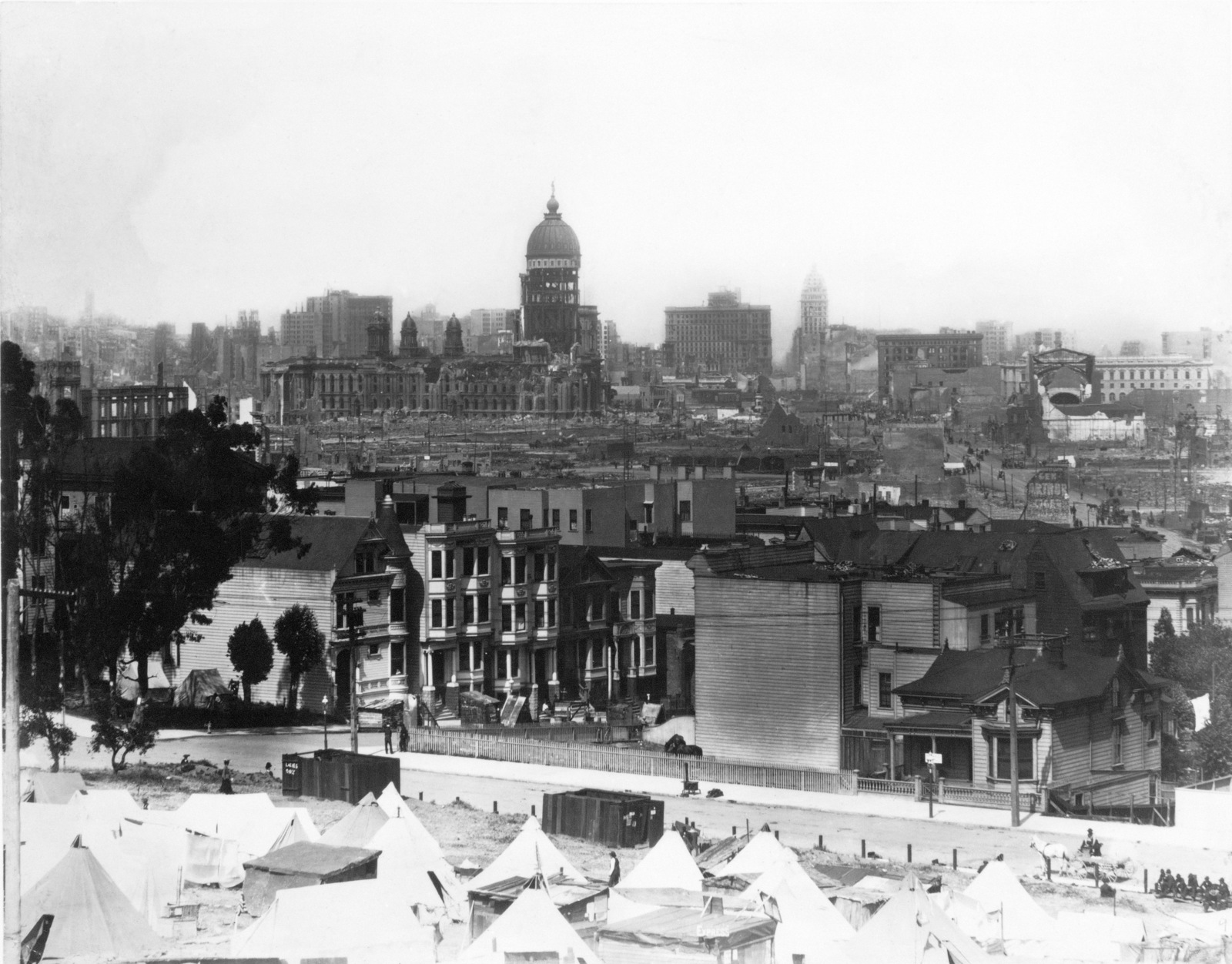 Refugee camp overlooks the damaged city of San Francisco. This camp might be on Mission Dolores Park. Note the Ladies and Mens facilities. In the distance are domes of the City Hall (left) and the Call Building (right). On April 18, 1906 at 5:15 AM a quake of 8.25 on the Richter scale hit San Francisco. Greater destruction came from the fires afterwards. The city burned for three days. The combination destroyed 490 city blocks and 25,000 buildings, leaving 250,000 homeless and killing between 450 and 700. Estimated damages, over $350 million