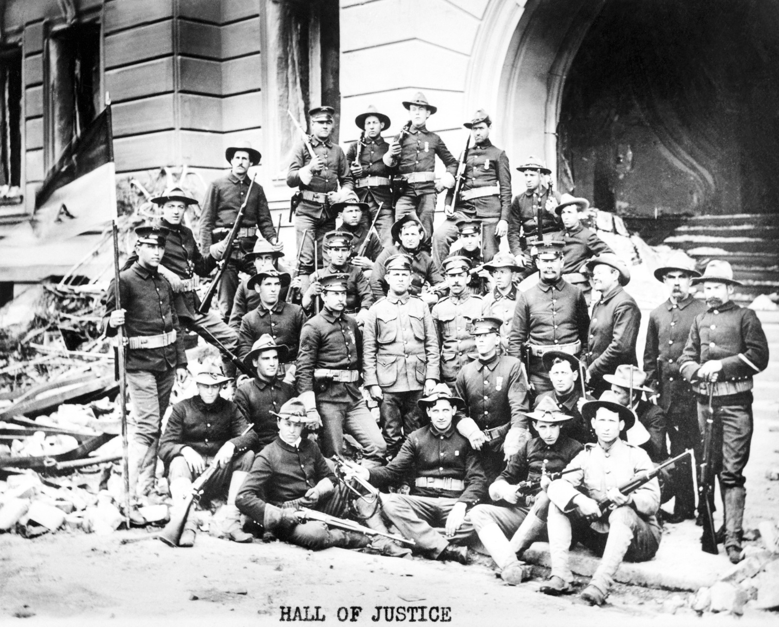 US Army soldiers from the Presidio pose for a group shot, with their Springfield 03 rifles, in front of the ruins of the Hall of Justice. The troops aided the local police force in keeping order and protection for the citizens of the devastated city. On April 18, 1906 at 5:15 AM a quake of 8.25 on the Richter scale hit San Francisco. Greater destruction came from the fires afterwards. The city burned for three days. The combination destroyed 490 city blocks and 25,000 buildings, leaving 250,000 homeless and killing between 450 and 700. Estimated damages, over $350 million
