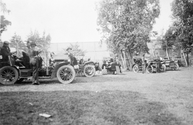 A gathering of autos, possibly a parking lot with chauffeurs and mechanics. On the left with the hood up is a 1907 Type H Locomobile 35 H.P. Touring Car. On the right, a pair of 1906 Cadillac Model M Light Touring Cars