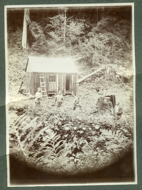 Photograph of Four Men Standing in Front of A Cabin