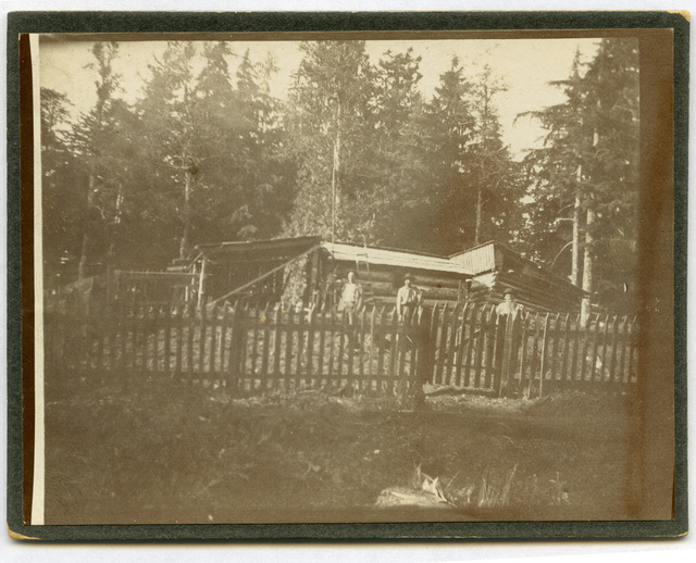 Photograph of Three Men Standing in Front of a Log Cabin Surrounded by a Fence