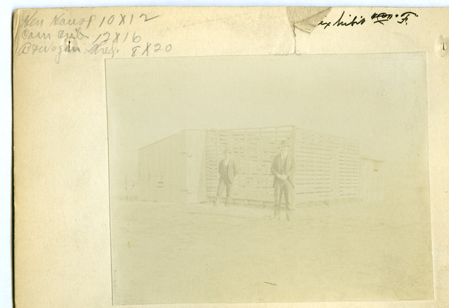Photograph of Two Men Standing in Front of Wooden Structure