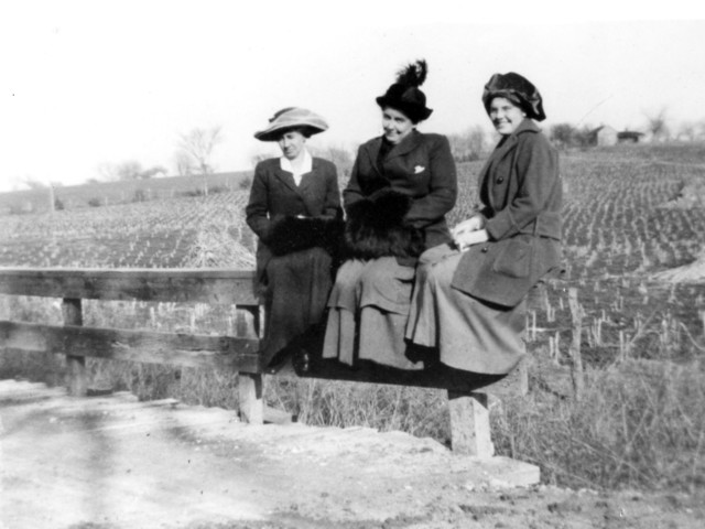 Photograph of Bess Wallace and Others Sitting on a Farm Fence