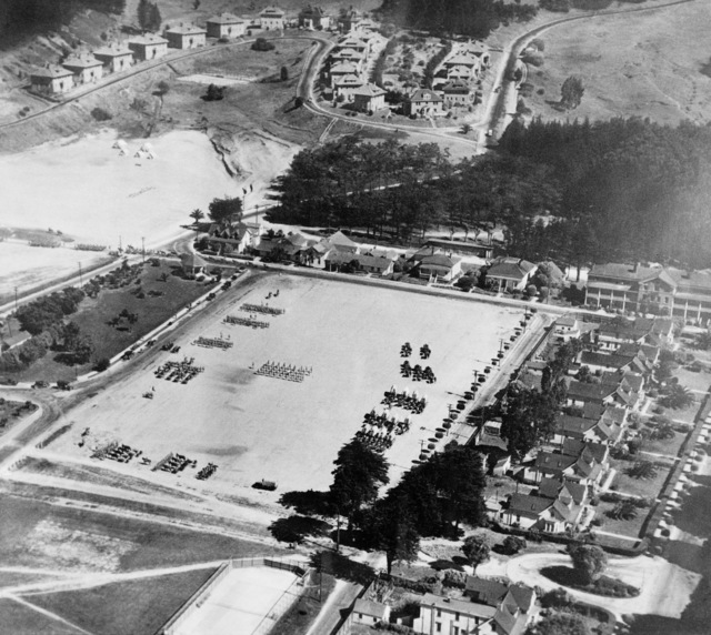 An aerial view of the parade ground at the Presidio with troops in review. From all the horse or mule drawn cannons and covered wagons this shot might be pre-WWI