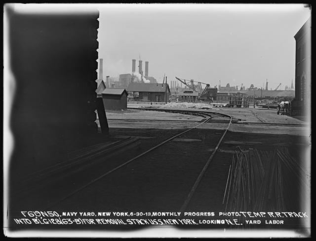 Monthly Progress Photo, Temporary Railroad Track into Building 128 (63-B) for Removal of U.S.S. New York Stack, Looking Northeast, Yard Labor