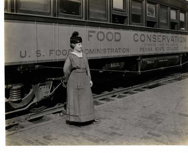 Photograph of Woman Standing in front of the Pennsylvania Food Conservation Train