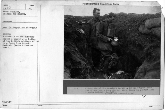 A Chaplain of the Munsters saying a prayer over bodies of two British soldiers killed in a front line trench. Cambrai. (Arras & Cambrai Area)