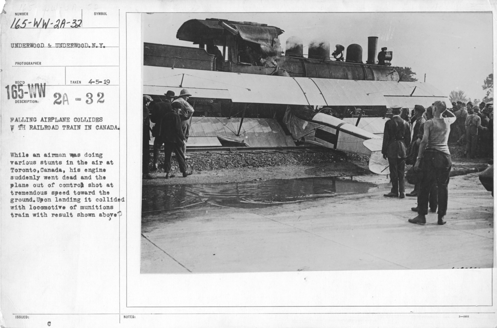 Airplanes - Accidents - Falling airplane collides with the railroad train in Canada. While an airman was doing various stunts in the air at Toronto, Canada, his engine suddenly went dead and the plane out of control shot at tremendous speed toward the ground. Upon landing it collided with locomotive of munitions train with result shown above
