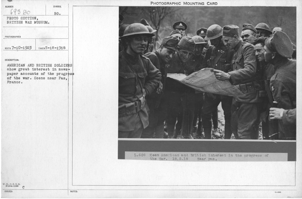 American and British soldiers show great interest in newspaper accounts of the progress of the war. Scene near Pas, France. 5-18-1918