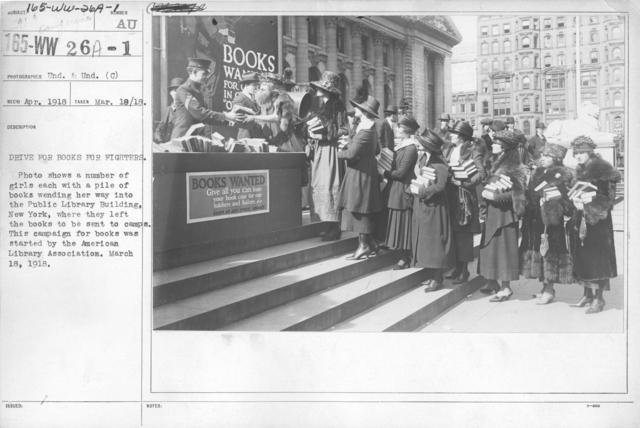 American Library Association - Campaigns - Drive for books for fighters. Photo shows a number of girls each with a pile of books wending her way into the Public Library Building, New York, where they left books to be sent to camps. This campaign for books was started by the American Library Association. March 18, 1918