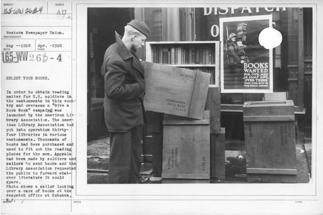 """American Library Association - Dispatch - Enlist your books. In order to obtain reading matter for U.S. soldiers in the cantonments in this country and overseas a """"Give a Book Week"""" campaign was launched by the American Library Association. The American Library Association had put into operation thirty-four libraries in various cantonments. Thousands of books had been purchased and used to fit out the reading places for the men. Appeals had been made by soldiers and saolors to send books and the Library Association requested the public to forward whatever literature it could spare. Photo shows a sailor looking over a case of books at the dispatch office at Hoboken, N.J"""