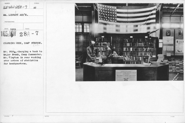 American Library Association - Libraries - Kansas through Mississippi - Charging Desk, Camp Funston. Mr. Fitts, charging a book to Major Frank, Camp Commander. Mr. Clayton in rear working over orders of statistics for headquarters