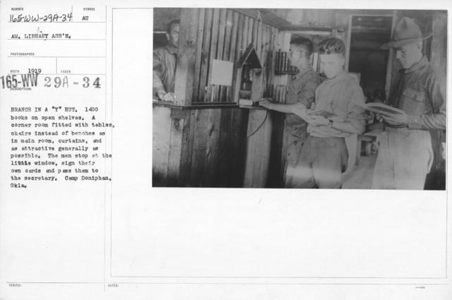 """American Library Association - O through R - Branch in a """"Y"""" Hut. 1400 books on open shelves. A corner room fitted with tables, chairs instead of benches as in main room, curtains, and as attractive generally as possible. The men stop at the little window, sign their own cards and pass them to the secretary. Camp Doniphan, Okla"""