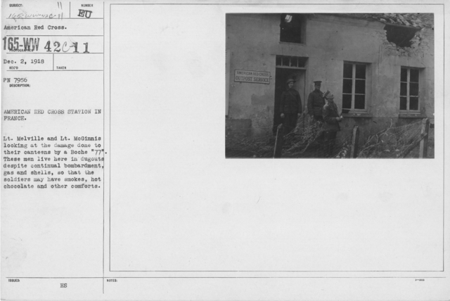 """American Red Cross - Canteens - American Red Cross Station in France. Lt. Melville and Lt. McGinnis looking at the damage done to their canteens by a Boche """"77"""". These men live here in dugouts despite continual bombardment, gas and shells, so that the soldiers may have smokes, hot chocolate and other comforts"""
