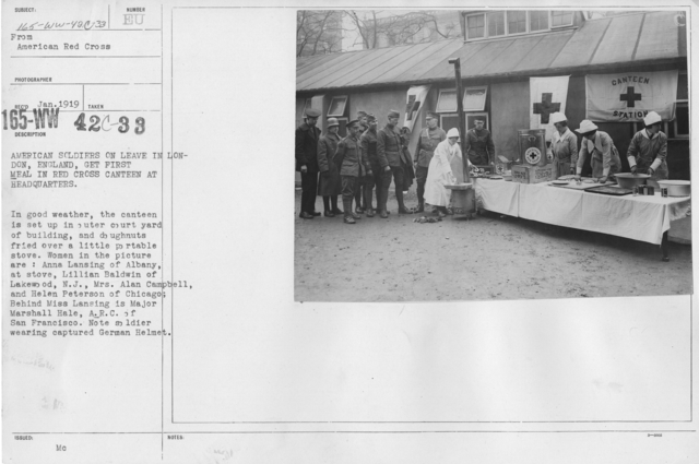 American Red Cross - Canteens - American soldiers on leave in London, England, get first meal in Red Cross Canteen at Headquarters. In good weather, the canteen is set up in outer courtyard of building, and doughnuts fried over a little portable stove. Women in the picture are: Anna Lansing of Albany, at stove, Lillian Baldwin of Lakewood, N.J., Mrs. Alan Campbell, and Helen Peterson of Chicago; Behind Miss Lansin is Major Marshall Hale, A.R.C. of San Francisco. Not soldier wearing captured German Helmet