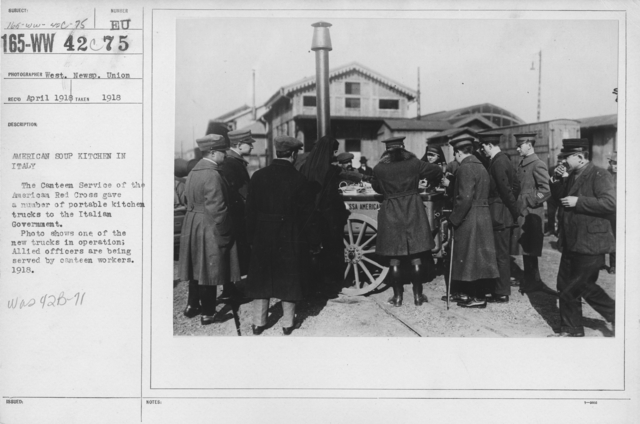 American Red Cross - Canteens - American soup kitchen in Italy. The Canteen Service of the American Red Cross gave a number of portable kitchen trucks to the Italian Government. Photo shows one of the new trucks in operation; Allied officers are being served by canteen workers. 1918