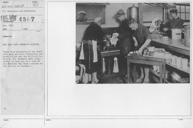 American Red Cross - Canteens - One good turn deserves another. These fine specimens of the American Army and Navy (including the Naval Police and the Military Police at the dishpan) have volunteered to help out in a rush at the American Red Cross canteen at the station at Bordeauz