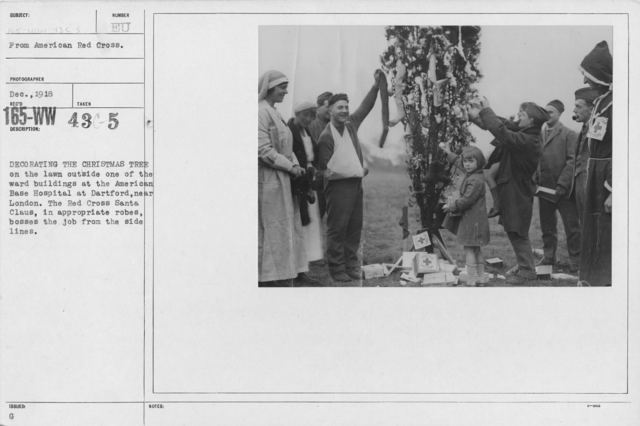 American Red Cross - Christmas Activities - Decorating the Christmas Tree on the lawn outside one of the ward buildings at the American Base Hospital at Dartford, near London. The Red Cross Santa Claus, in appropriate robes, bosses the job from the side lines