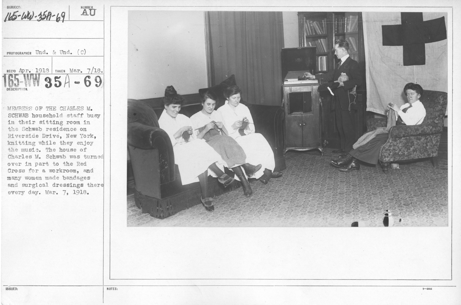 American Red Cross - Classes in Red Cross Work - Members of the Charles M. Schwab household staff busy in their sitting room in the Schwab residence on Riverside Drive, New York, knitting while they enjoy the music. The house of Charles M. Schwab was turned over in part to the Red Cross for a workroom, and many women made bandages and surgical dressings there every day