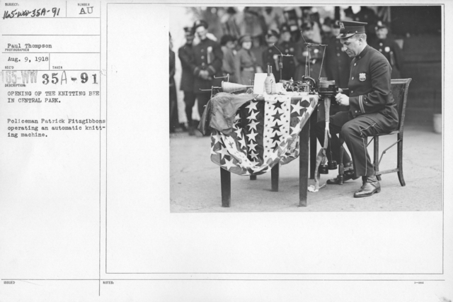 American Red Cross - Classes in Red Cross Work - Opening of the Knitting Bee in Central Park. Policeman Patrick Fitzgibbons operating an automatic knitting machine