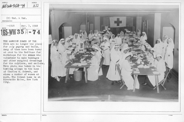 American Red Cross - Classes in Red Cross Work - The mansion homes of the rich are no longer the place for only gayety and balls. Many of them have been turned over to the Red Cross for workshops for the women who volunteer to make bandages and other surgical dressings for the soldiers and sailors. This photo was taken in the bowling alleys in the home of Charles M. Schwab, and shows a number of women at work. The Schwab home is at Riverside Drive, New York City