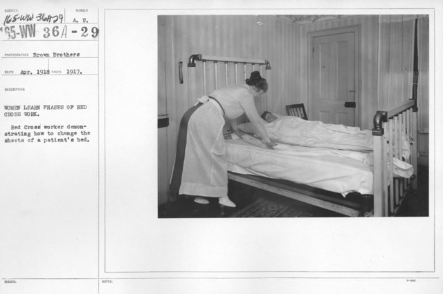 American Red Cross - Classes in Red Cross Work (workrooms and classes) - Women learn phases of Red Cross work. Red Cross worker demonstrates how to change the sheets of a patient's bed