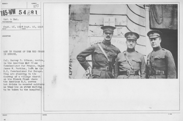 American Red Cross - E thru H - Men in charge of the Red Cross in Europe. Col. Harvey D. Gibson, center is the American Red Cross Commissioner for France. Major James W. Perkins, left is the R.C. Commissioner for Europe. They are standing in the doorway of a village church on the French front where the American R.C. serves hot drinks to wounded soldiers as they lie on straw waiting to be taken to the hospital