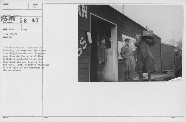 American Red Cross - Groups - Captain Harry D. Kirover of Buffalo, the American Red Cross District Commander at Liverpool superintends the work of distributing comforts to wounded Americans who are leaving for the U.S., Capt. Kirkover standing at the left of the entrance of the warehouse