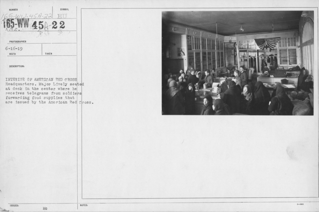 American Red Cross - Headquarters & Buildings - Interior of American Red Cross Headquarters. Major Lively seated at desk in the center where he receives telegrams from soldiers forwarding food supplies that are issued by the American Red Cross