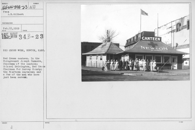 American Red Cross - In the Service of Interior - Canteen Service - Red Cross Work, Newton, Kans. Red Cross canteen. In the foreground: Joseph Summers, Chairman of the canteen; Colonel Hoisington, Red Cross Chairman for Harvey County; the fourteen captains; and a few of the men who have just been served