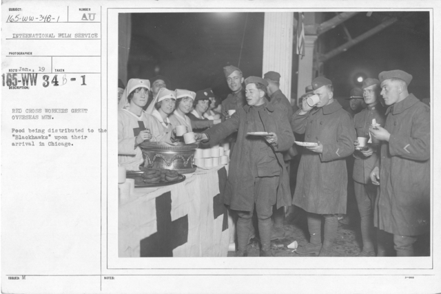 """American Red Cross - In the Service of Interior - Canteen Service - Red Cross workers greet overseas mean. Food being distributed to the """"Blackhawks"""" upon their arrival in Chicago. International Film Service"""