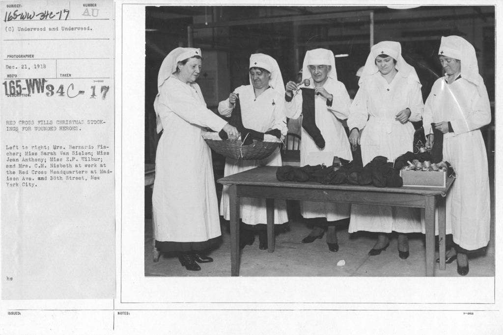 American Red Cross - In the Service of Interior - Christmas Boxes - Red Cross Fills Christmas stockings for wounded heroes. Left to right: Mrs. Bernardo Fisher; Miss Sarah Van Sielen; Miss Jean Anthony; Miss Z.P. Wilbur; and Mrs. C.M. Nisbeth at work at the Red Cross Headquarters at Madison Ave. and 38th Street, New York City