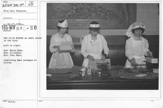 American Red Cross - In the Service of Interior - Christmas Boxes - Red Cross nurses as Santa Claus in New York. Left to right: Mrs. Harry Lake, Mrs. E.C. Mogee, Mrs. John Soxe, inspecting Christmas packages at armory