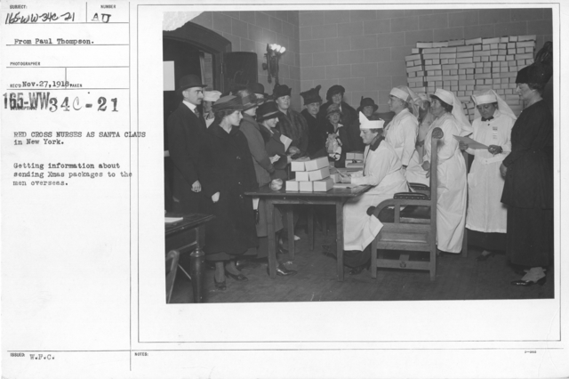 American Red Cross - In the Service of Interior - Christmas Boxes - Red Cross nurses as Santa Claus in New York. Getting information about sending Christmas packages to the men overseas