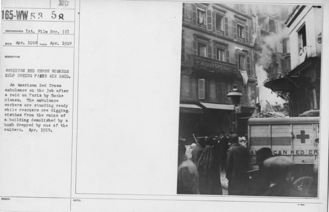 American Red Cross - Miscellaneous - American Red Cross Workers help during Pairs Aid Raid. An American Red Cross ambulance on the job after a raid on Paris by Boche planes. The ambulance workers are standing ready while rescuers are digging victims from the ruins of a building demolished by a bomb by one of the raiders. April. 1918