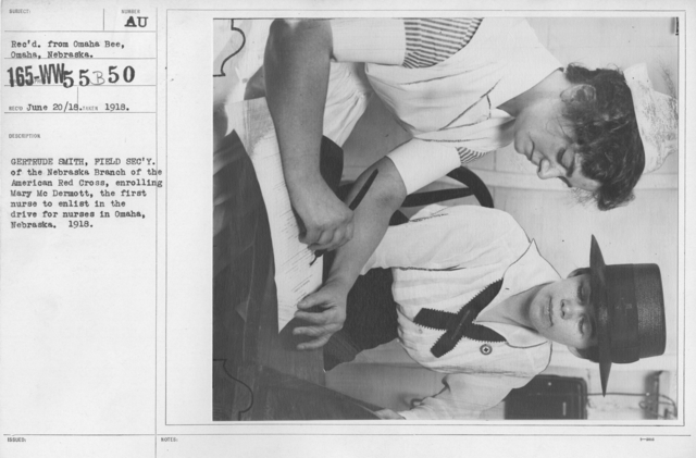 American Red Cross - N thru W - Gertrude Smith, Field Secretary of the Nebraska Branch of the American Red Cross, enrolling Mary McDermott, the first nurse to enlist in the drive for nurses in Omaha, Nebraska. 1918