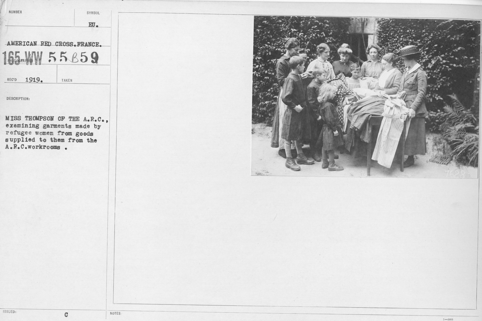 American Red Cross - N thru W - Miss Thompson of the A.R.C. examining garments made by refugee women from goods supplied to them from the A.R.C. workrooms