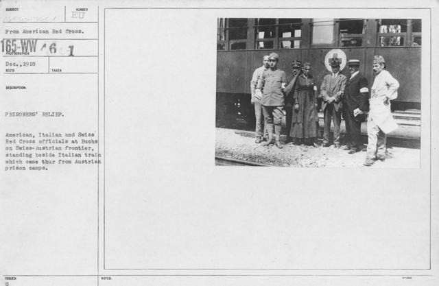 American Red Cross - Prisoners of War - Prisoners' relief. American, Italian and Swiss Red Cross officials at Buchs on Swiss-Austrian frontier, standing beside Italian train which came through from Austrian prison camps