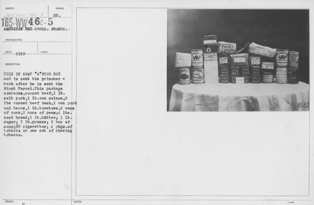 """American Red Cross - Prisoners of War - This is Army """"A"""" food box and is sent the prisoner a week after he is sent the First Parcel. This package contains corned beef, 1lb salt pork, 1lb can slamon, 2lbs corned beef hash, 1 can pork and beans, 1lb tomatoes, 2 cans of corn, 2 cans of peas, 3lbs hard bread; 1lb butter; 1lb sugar; 1lb prunes; 1 bar of soap; 80 cigarettes; 4 pkgs of tobacco or one cut of chewing tobacco"""