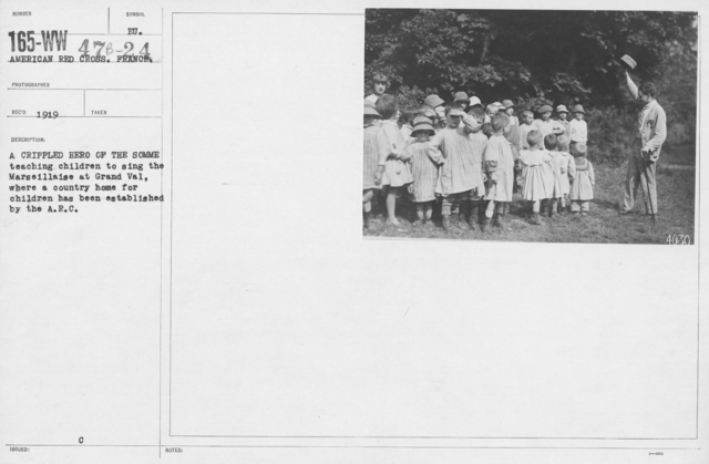 American Red Cross - Refugees - A crippled hero of the Somme teaching children to sing the Marseillaise at Grand Val, where a country home for children has been established by the A.R.C