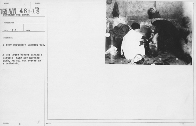American Red Cross - Refugees - A tiny refugee's morning tub. A Red Cross Worker giving a refugee baby her morning bath. An oil can serves as a bath tub