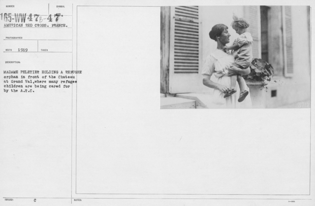 American Red Cross - Refugees - Madame Peletier holding a refugee orphan in front of the Chateau at Grand Val, where many refugee children are being cared for by the A.R.C