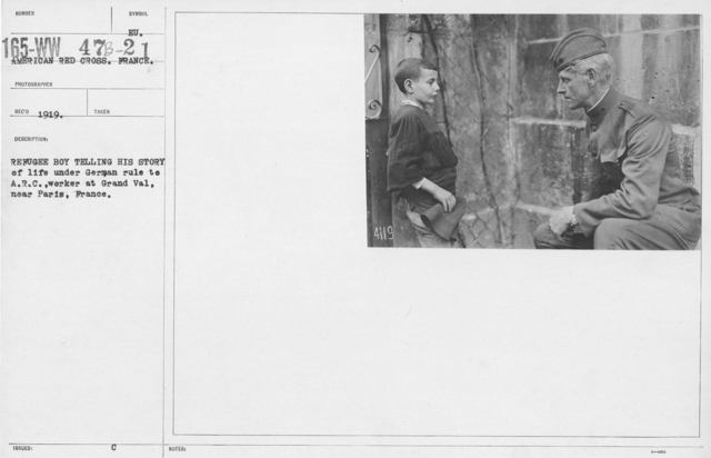 American Red Cross - Refugees - Refugee boy telling his story of life under German rule to A.R.C. worker at Grand Val, near Paris, France